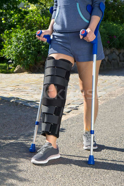 Woman wearing a leg brace walking on crutches Stock photo © belahoche