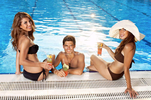 Three beautiful people at the pool Stock photo © belahoche