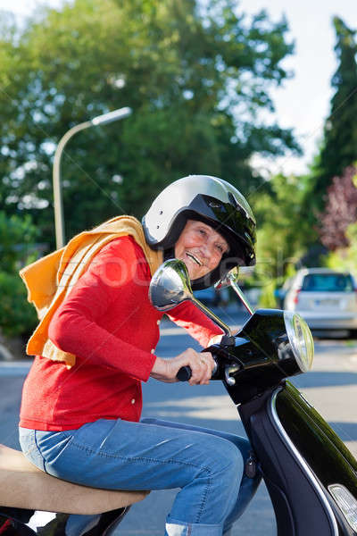 Vivacious elderly woman riding a scooter Stock photo © belahoche