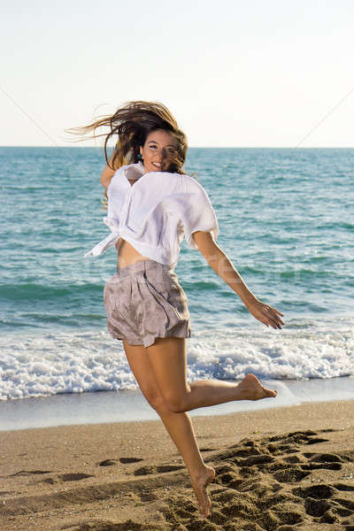 Young Female Jumping at the Beachfront Stock photo © belahoche