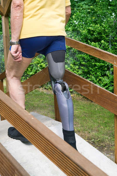 Unidentifiable man going over ramp with false leg at exercise course. Stock photo © belahoche
