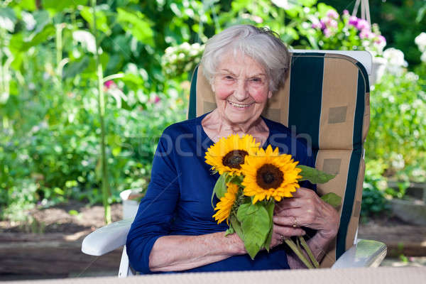 Happy Old Lady Sitting on Chair Holding Sunflowers Stock photo © belahoche