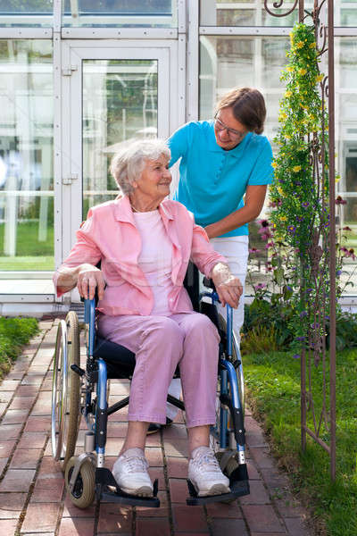 Elderly lady in a wheelchair with her carer Stock photo © belahoche