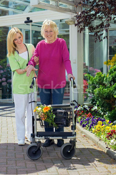 Nurse Helping Senior Woman to Walk with Walker Stock photo © belahoche