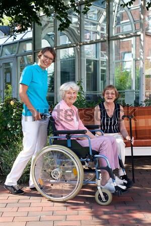 Genç hemşire tekerlekli sandalye gülen kamera Stok fotoğraf © belahoche