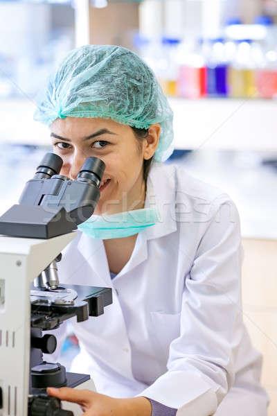 Friendly female lab technician using a microscope.  Stock photo © belahoche
