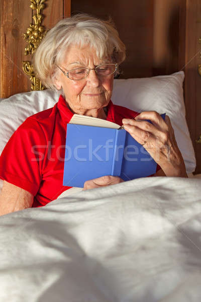 Senior woman reading in bed Stock photo © belahoche