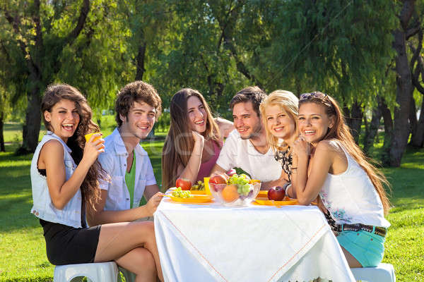 Happy students full of vitality eat a fruity meal Stock photo © belahoche
