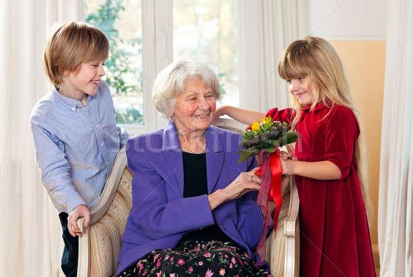Oma Blumen Enkelkinder schauen Familie ältere Stock foto © belahoche