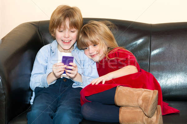 Two young children playing with a mobile phone Stock photo © belahoche