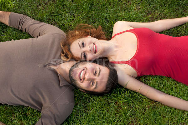 Happy couple in love laying down on the grass Stock photo © belahoche