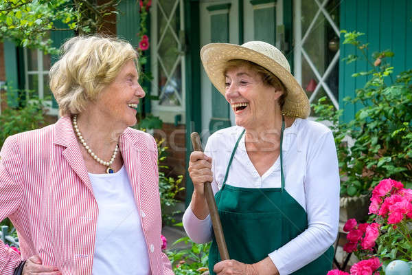 Two Senior Women Laughing Together in Garden Stock photo © belahoche