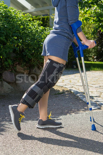 Young woman wearing a leg brace, side view Stock photo © belahoche