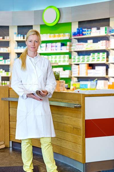 Cute pharmacist standing near counter Stock photo © belahoche