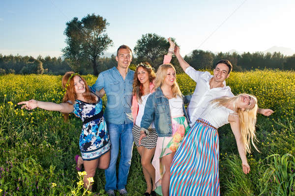 Group of happy young people posing in rapeseed Stock photo © belahoche