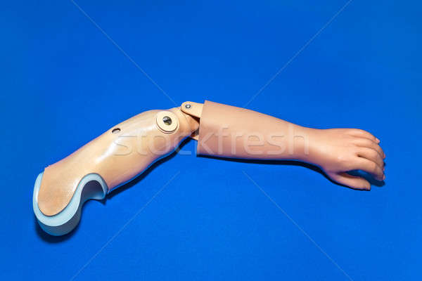 Single prosthetic arm over blue background Stock photo © belahoche