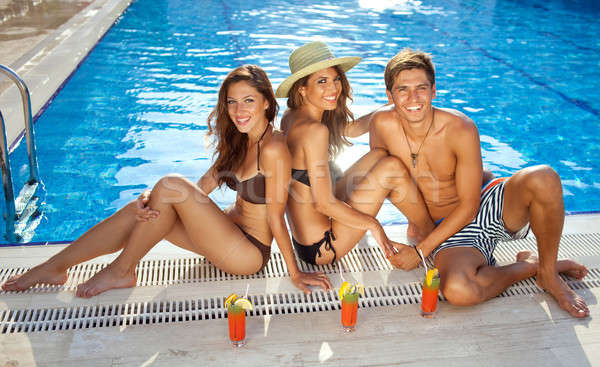 Friends sunbathing at the edge of a pool Stock photo © belahoche