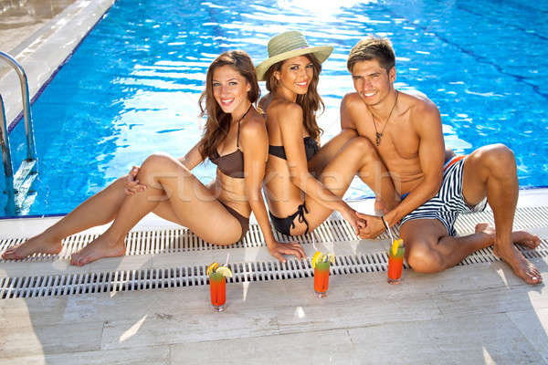 Friends enjoying drinks at the pool Stock photo © belahoche