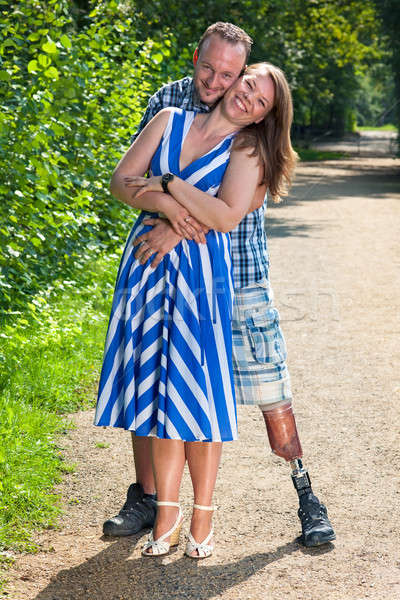 Disabled man and attractive woman in loving hug Stock photo © belahoche