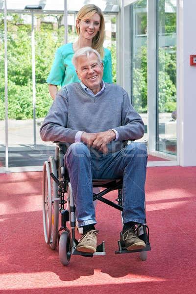 Portrait infirmière poussant supérieurs homme fauteuil roulant Photo stock © belahoche