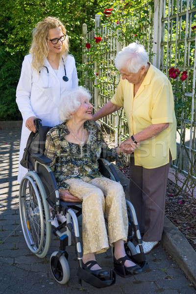 Idős orvos beszél gondozó boldog mozgássérült Stock fotó © belahoche