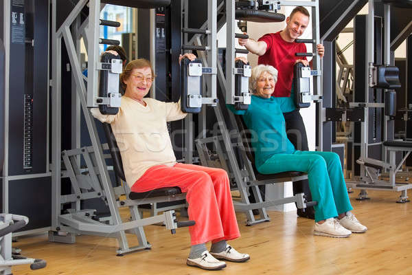 Smiling Elderly Women at the Gym with Instructor Stock photo © belahoche
