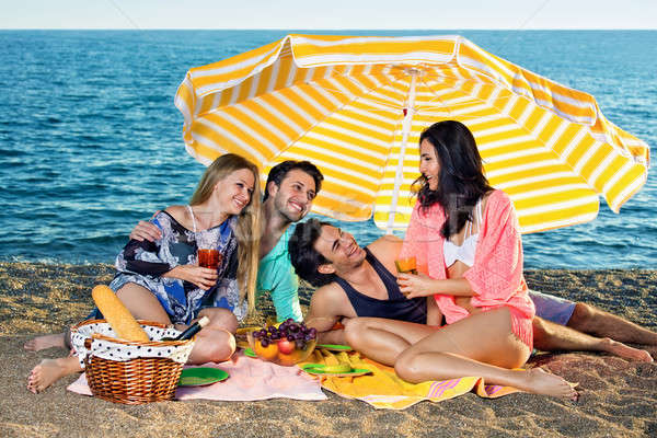 Four friends share food and drinks on the beach Stock photo © belahoche