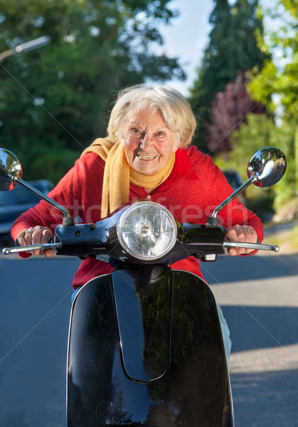 Elderly lady having fun on her scooter Stock photo © belahoche