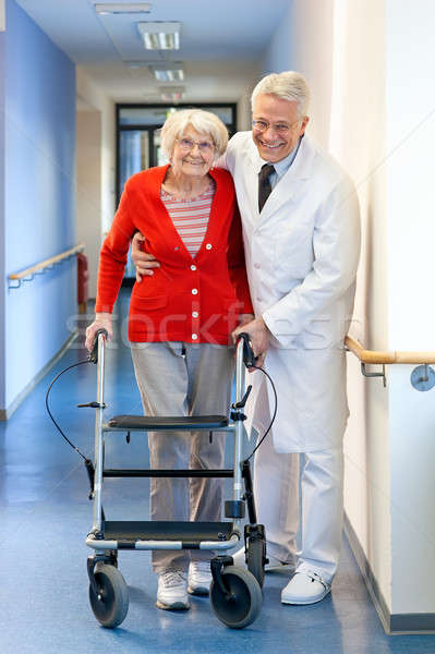 Physician helping a senior woman in a walker Stock photo © belahoche