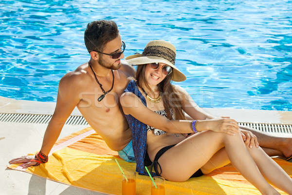 Loving couple relaxing in the sun at the pool Stock photo © belahoche