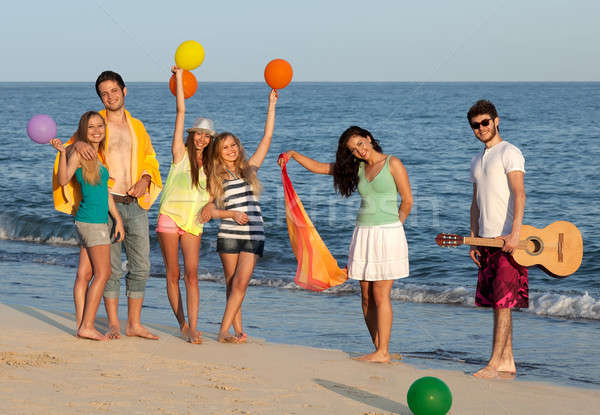 Group of young people enjoying beach party with guitar and ballo Stock photo © belahoche