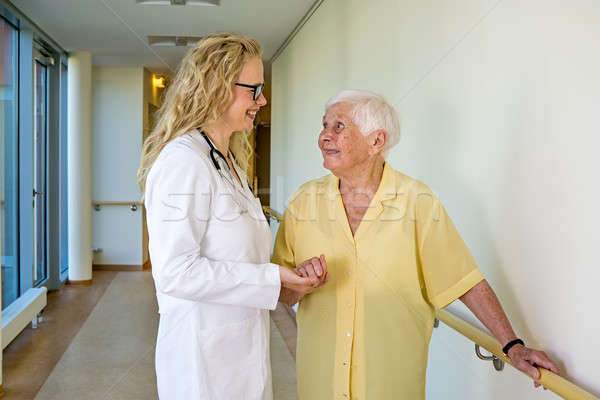 Nurse Supporting an Old Woman Walking at Corridor Stock photo © belahoche
