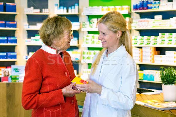 Friendly pharmacist giving customer prescription Stock photo © belahoche