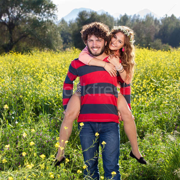 Young man giving his girlfriend a piggy back Stock photo © belahoche