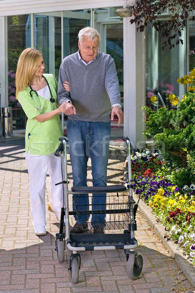 Nurse Helping Senior Man with Walker Outdoors Stock photo © belahoche