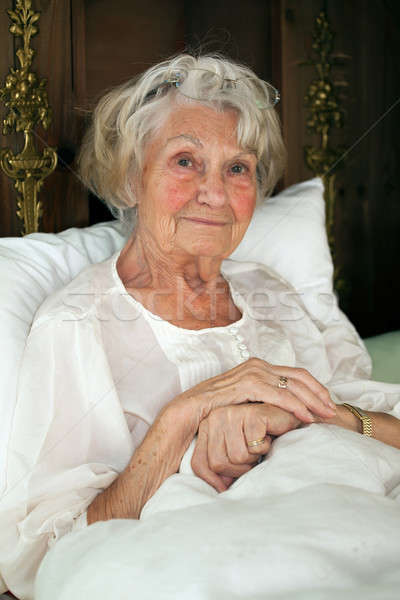 Stock photo: Senior woman resting in bed