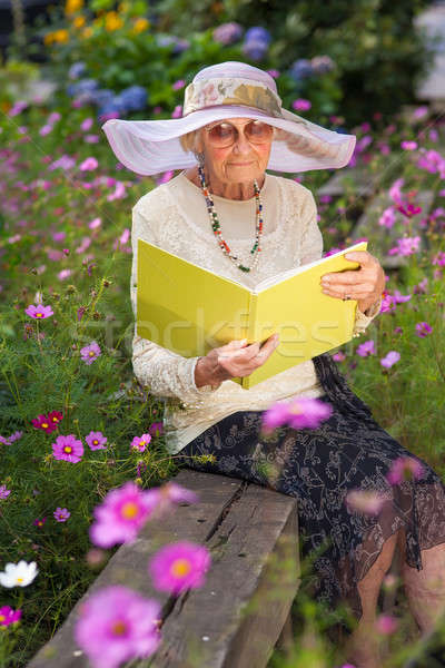 Fashionable old lady reading in her garden Stock photo © belahoche