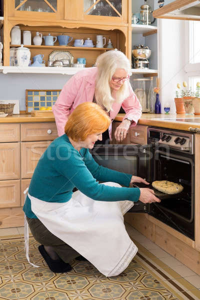 Mom Watching Other Mom Putting Cake in an Oven Stock photo © belahoche