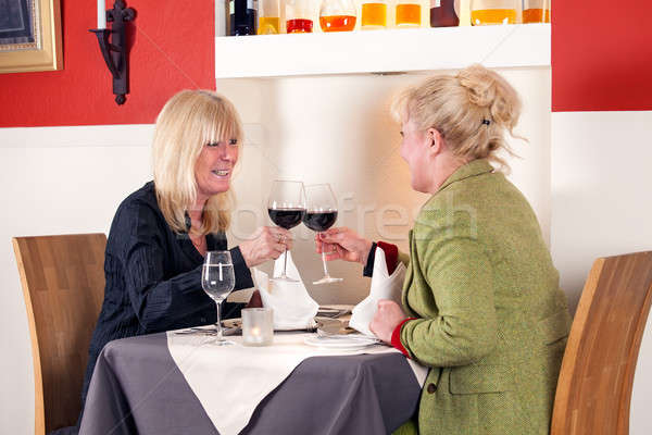 Two blond woman toasting with red wine Stock photo © belahoche