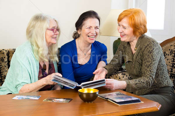 Adult Women Friends Laughing at Old Photos Stock photo © belahoche
