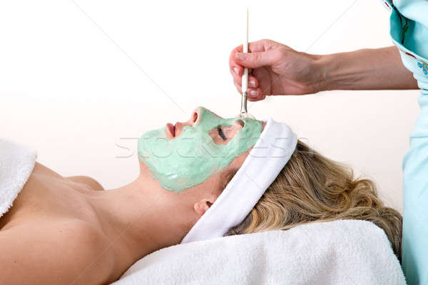 Beautician applying green facial mask on a woman. Stock photo © belahoche