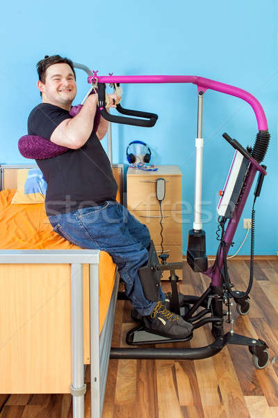 Young man with cerebral palsy using a patient lift Stock photo © belahoche