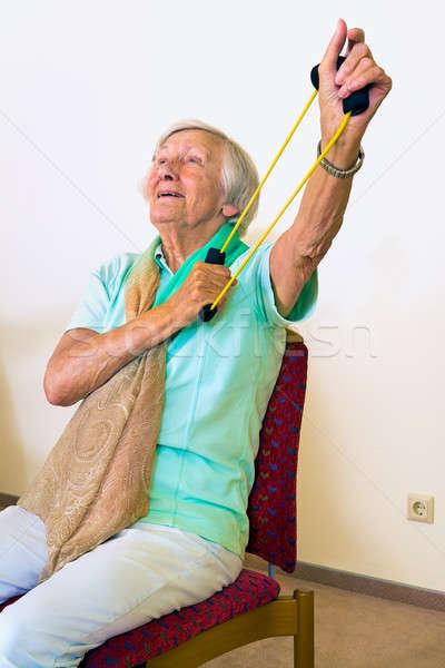 Elderly woman exercising her shoulders Stock photo © belahoche
