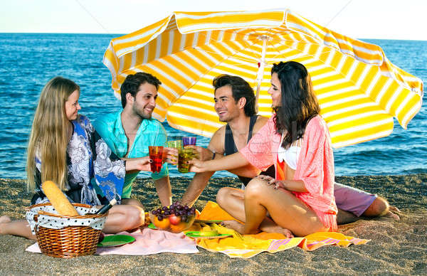 Two couples toast under an umbrella on the beach Stock photo © belahoche