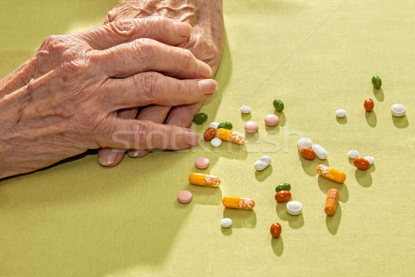 Hands of an elderly lady with medication Stock photo © belahoche