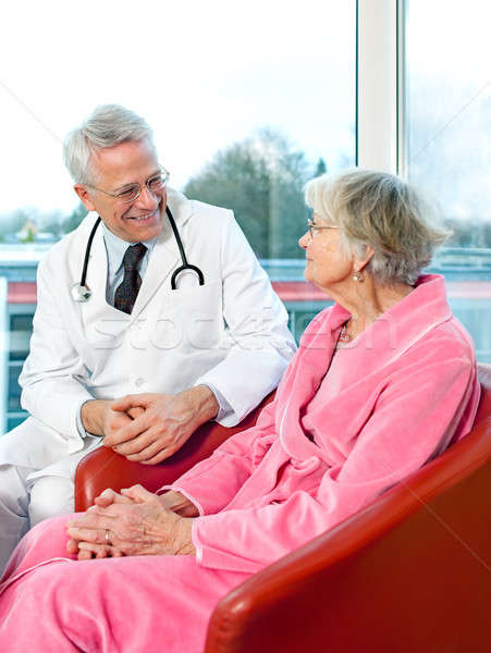 Friendly senior male doctor chatting to a patient Stock photo © belahoche