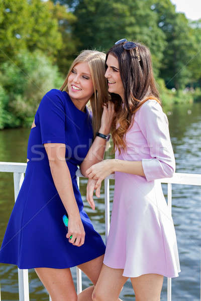 Two female friends watching somebody.  Stock photo © belahoche