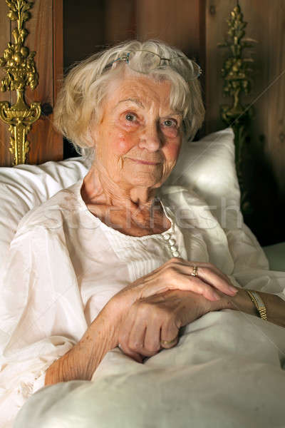 Senior lady in her nightgown in bed Stock photo © belahoche