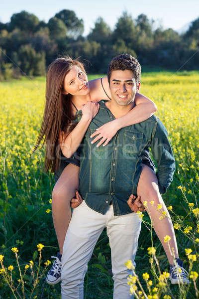 Happy smiling couple enjoy a piggy back ride Stock photo © belahoche