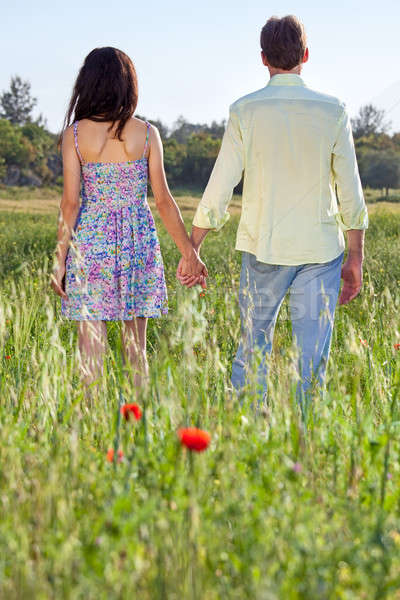 Young couple walking through a poppy field Stock photo © belahoche